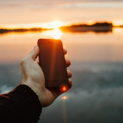 Man holding an Iphone 4, in front of a sunset over water