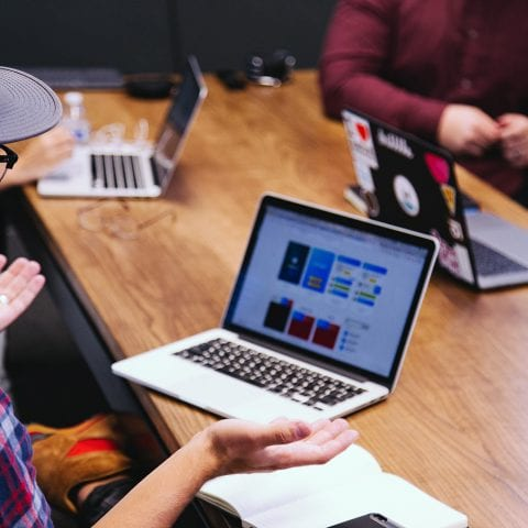Man wearing baseball cap, holding a Macbook at a meeting