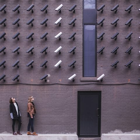 A wall full of security cameras, with two women standing below