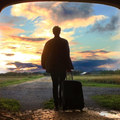 Man with luggage, looking into a colourful sky in the countryside