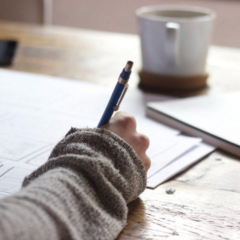 Person wearing grey cardigan, writing on A4 paper at wooden desk