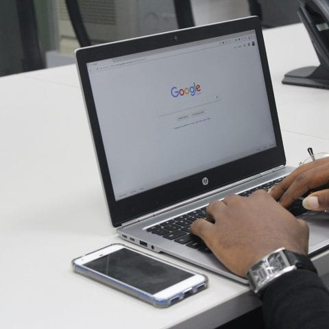 Man using Google Search on a HP laptop