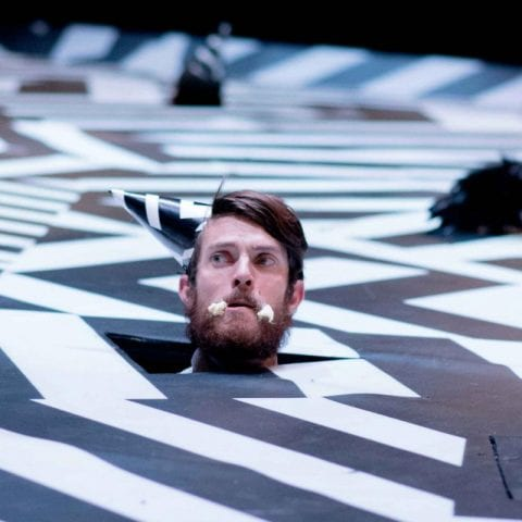 Man wearing hat pokes his head through surreal abstract set