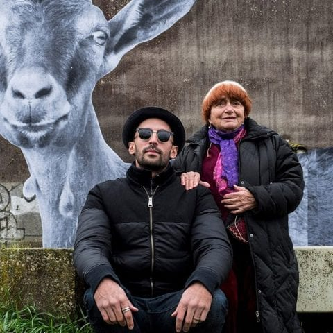Man wearing black shades, with older lady, with graffiti art goat in background