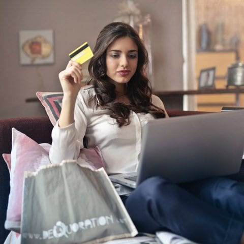 Women, sitting on a sofa, holding a credit card, with laptop on lap