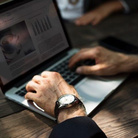 Man using a laptop on a dark wooden desk