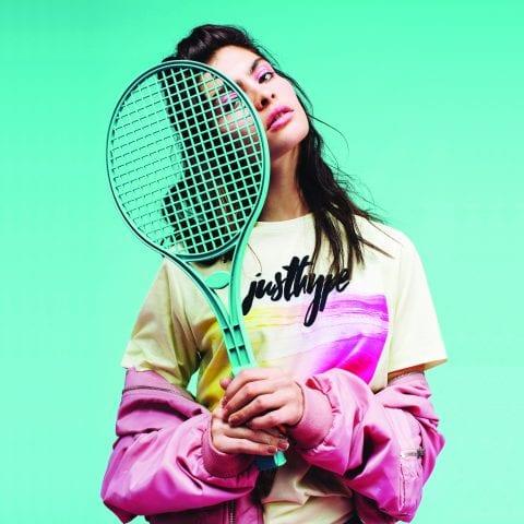 Fashion model wearing Hype clothing, holding tennis racket