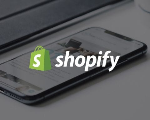 Shopify logo, with smartphone in background