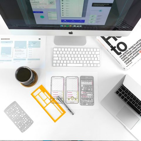 White desk with various objects used for UX design