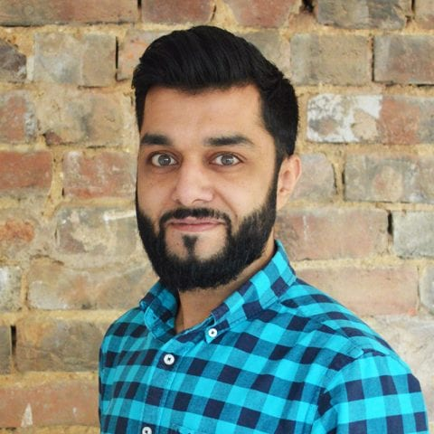 Sanjay Katwa, wearing blue check shirt in front of brick wall