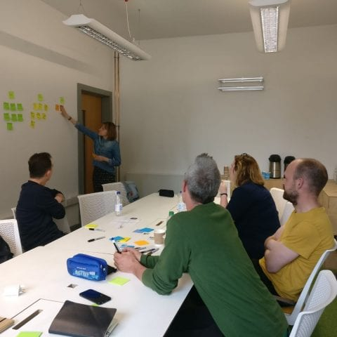 A work meeting, with sticky notes on the wall