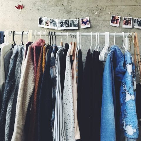 Rail of fashionable women's clothes, against a stone wall