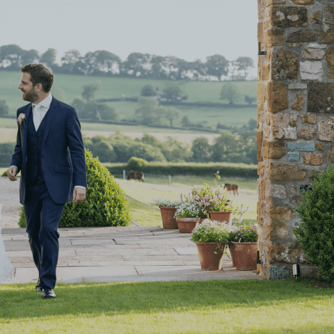 Happy couple, dressed for a wedding in the English countryside.