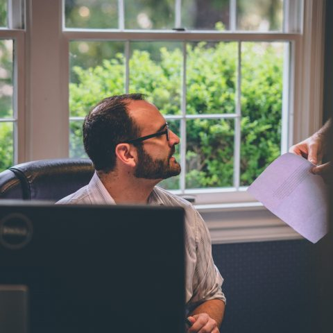 Person sitting as desk, chatting with colleague