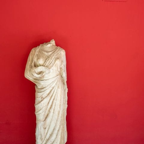 A headless statue on a red background