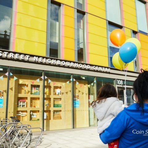 woman with a girl and balloon standing in front of the coin street neighbourhood centre