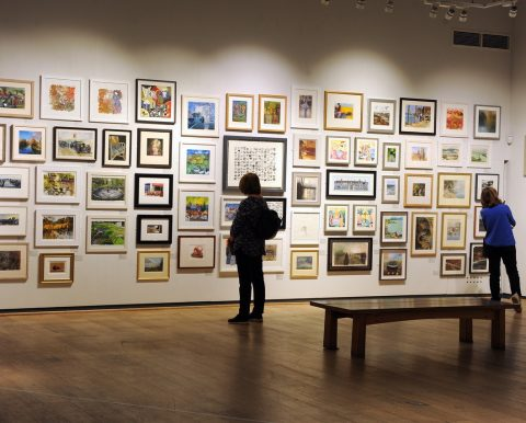 Visitors browsing the artwork at Mall Galleries
