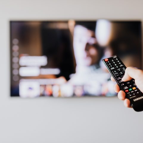 A person with a remote control watching an event on their television