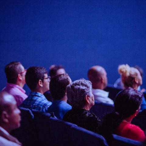A Cinema with people sat watching a screen