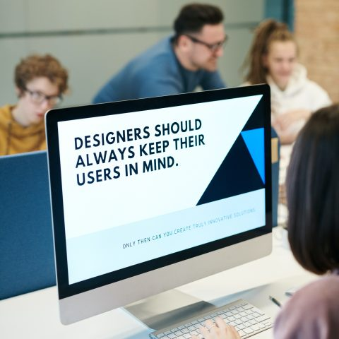 A designer reading a computer screen which says 'Designers should always keep their users in mind'